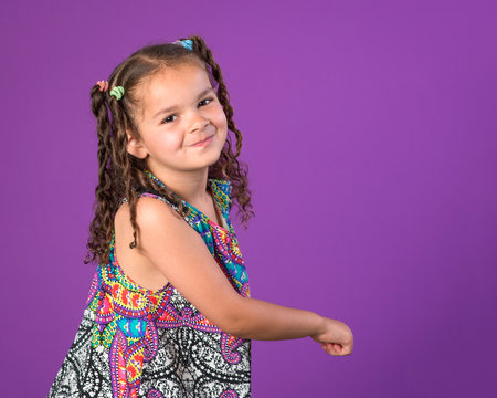 Smiling little girl dancing spinning playing isolated on purple background