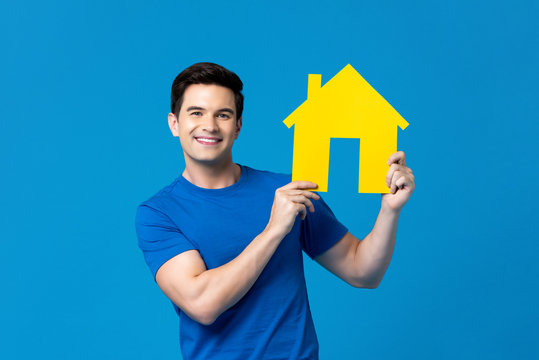 Smiling handsome caucasian man holding  house model