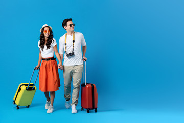Fototapeta Young couple going for holidays with colorful suitcases obraz