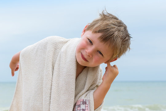 A little boy cleans his ear from the water by the sea, ocean.