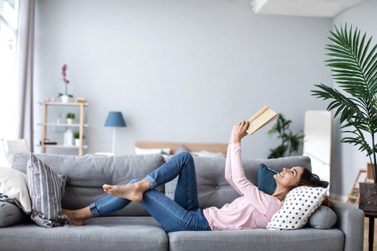 Beautiful smiling woman reading a book and lying on the sofa in the living room.