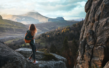 woman standing on edge of cliff against background of sunrise Wall mural