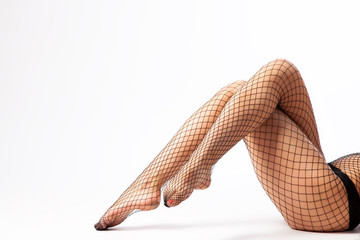 Close-up of beautiful woman's slim legs in nylon black tights in a mesh posing in an elegant pose on white isolated background. Concept of beauty woman posing for legs. Woman in hosiery.