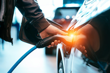 Human hand is holding Electric Car Charging connect to Electric car