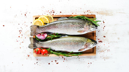 Fotomurales - Raw fish with vegetables on a white wooden background. Fish trout. Top view. Free space for your text.