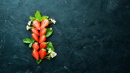 Fresh strawberry with leaves on a black stone background. Berries Top view. Free space for your text.