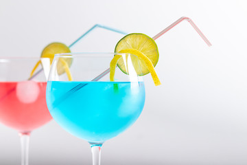 red and blue cocktail in a gin glass on a white background