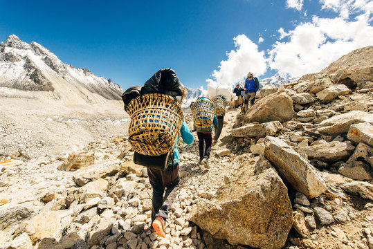 Porter and Sherpa walking with big bag baggage luggage in Himalaya Mountains in Nepal.