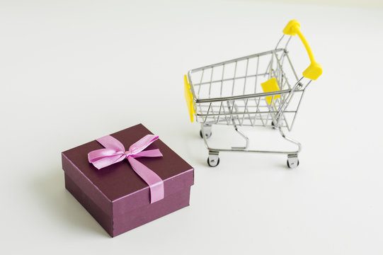 Small shoppinh cart toy and gift box with pink ribbon on white background. Shopping concept