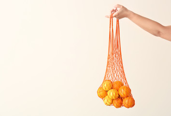 Female hand holding mesh eco bag with fruits on light background
