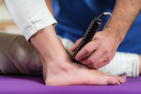 Laser Physical Therapy. Physical Therapist Treating Senior Woman's Foot