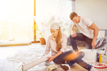 Couple with wallpaper while wallpapering and renovating