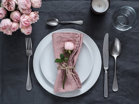 Beautiful table setting with candle on gray linen tablecloth. Festive table setting for wedding dinner with pink spray rose and pink napkin on plate. Holiday dinner with white plates