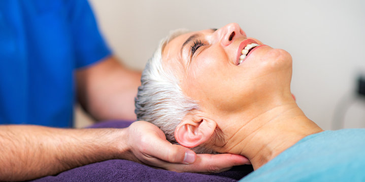 Physical Therapist Working with Neck. Senior Woman