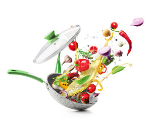 Cooking concept. Vegetables are flying out of the pan isolated on white background. Healthy food.