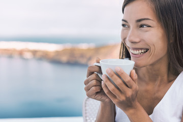 Wall Mural - Breakfast coffee girl drinking coffee cup in the morning looking at Mediterranean sea view from hotel or cruise ship balcony. Asian woman relaxing enjoying home lifestyle.