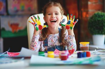 funny child girl draws laughing shows hands dirty with paint.