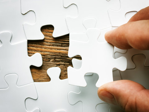 Hand with missing jigsaw puzzle piece. Business concept image for completing the final puzzle piece