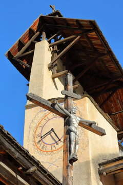 Close-up on the bell tower of Saint Sebastien Church with the Cross of Jesus Christ, Ceillac, Queyras Regional Natural Park, Southern Alps, France