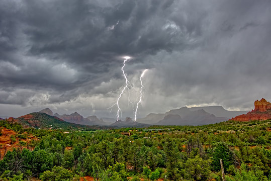 Lightning striking during a storm over Cibola Rock in Uptown, viewed from the Broken Arrow Trail, Sedona, Arizona