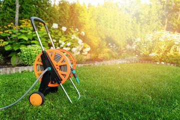 garden hose reel on green lawn in backyard copy space