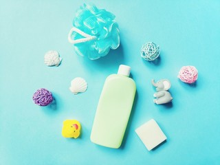 Flat lay shampoo for kids, baby soap, rubber toys and sponge on a blue background. Natural organic cosmetics