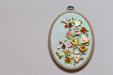 Close up view for the hand embroidery with satin, silk and nylon ribbons of flower ornament with delicate roses on hoop (the embroidery made the author of photo)
