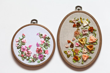 Close up view of two handmade embroidery with satin ribbons of floral ornaments with roses on the embroidery frames on a white background (embroidery made by the author of the photo)