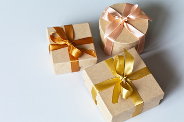 Three gift boxes tied with delicate satin ribbons with presents for a family holiday