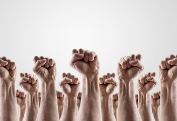 Large group of raised hands showing fists