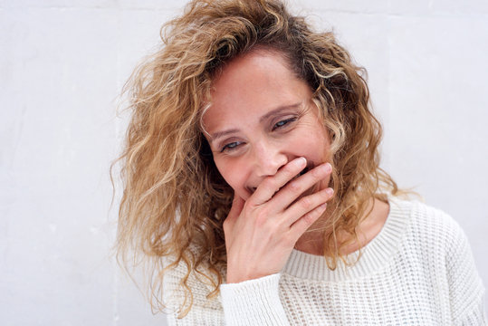 Close up happy middle age woman laughing with hand covering mouth