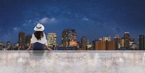 Wall Mural - Woman in white hat and clothes sitting on rooftop floor, looking Osaka city at night with sky full of stars