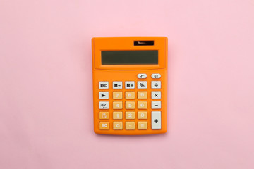Orange calculator on a bright paper pink background. Office supplies. Education. back to school. top view.