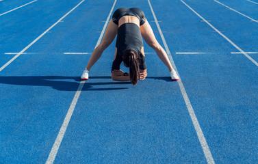 Sportswoman stretching before run on stadium