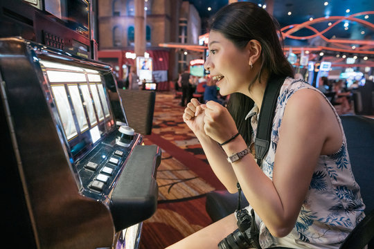 cheerful young girl tourist playing slot machine in casino. Concentrated woman traveler with camera sitting and having fun with gambling in night las vegas nevada. summer luxury trip in america.