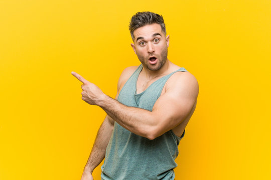 Young fitness man against a yellow background pointing to the side