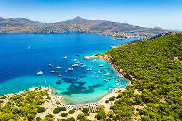 Wall Mural - Der beliebte Strand auf der kleinen Insel Moni gegenüber von Perdika bei Ägina mit türkisem Meer und zahlreichen Segelbooten, Griechenland