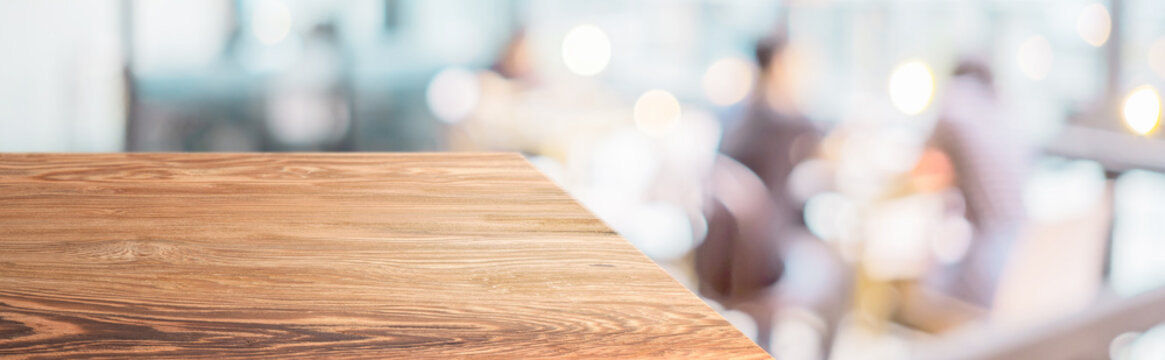 Perspective wood table with blur cafe restaurant with people dining background bokeh light.Panoramic wooden countertop banner mock up for advertising and product display design online content.