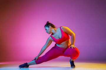 Young caucasian plus size female model's doing exercises on gradient purple background in neon light. Training in lunges and stratching. Concept of sport, healthy lifestyle, body positive, equality.