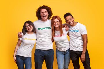 Happy multiethnic volunteers hugging each other