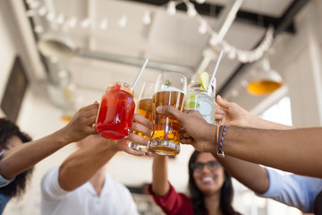 leisure, food and people concept - group of happy international friends clinking glasses at bar or restaurant