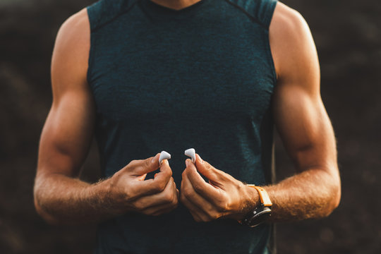 Man holding air pods headphones in hands close-up. Athletic muscles body and dark background. Innovation technology concept.