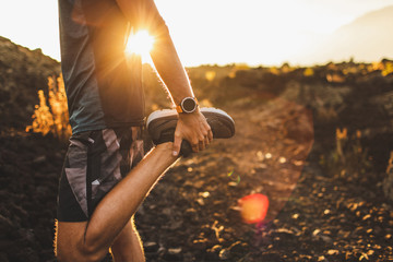 Male runner stretching leg and feet and preparing for running outdoors. Smartwatches or fitness tracker on hand. Beautiful sun light on background. Active and healthy lifestyle concept. Fotoväggar