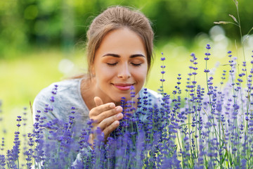gardening and people concept - happy young woman smelling lavender flowers at summer garden