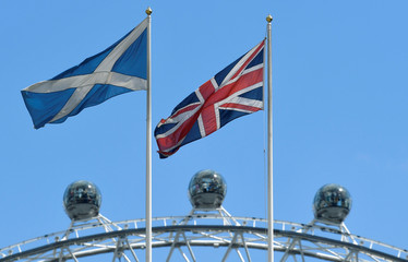 The Scottish Saltire flag flies next to the British Union Jack flag with the London Eye wheel seen behind in London