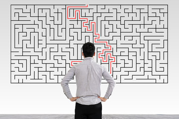 Fototapeta Businessman in doubt looking to a maze and searching the way out obraz