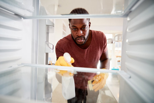 View Looking Out From Inside Empty Refrigerator As Man Wearing Rubber Gloves Cleans Shelves