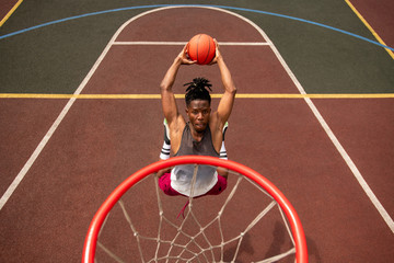 African young basketballer making effort while throwing ball in basket
