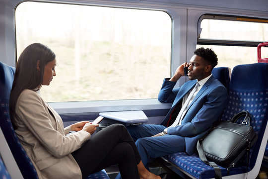 Business Passengers Sitting In Train Commuting To Work Using Mobile Phones