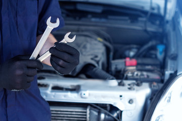 Repairman is repairing car at service station. Closeup mechanic hands in gloves are holding steel wrenches. Vehicle with open hood on background.  Modern auto repair shop with equipments and  tools.